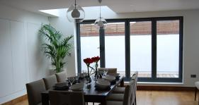 A 4 door bi fold in grey gives this dining area a light and airy appearance