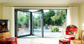 3 part bi folding door set in RAL 7021 used at the end of a lounge to bring light into the room and open out into the garden
