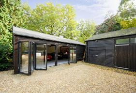 4 part bi - folding door system in black grey blends in perfectly with the woodland setting whilst demonstrating a perfect alternative use of the product